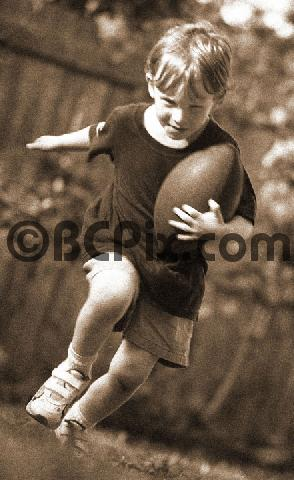Product picture A little boy runs with a football, sepia tone