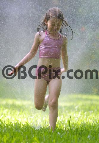Product picture A girl runs through a sprinkler
